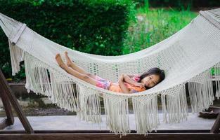 kleines asiatisches Mädchen im Kleid, das auf die Wiege legt foto