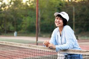 schöne asiatische frau mit kurzen haaren, mit hut und breitem lächeln auf tennisplatz foto