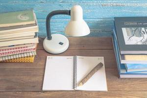 Arbeitsplatz mit Leselampe und Büchern auf altem Holztisch. Vintage-Konzept foto