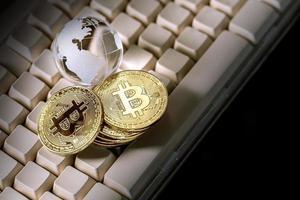 Glaskugel und Bitcoin-Kryptowährung auf der Tastatur. Geschäftskonzept foto