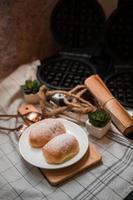 weiches Butterbrötchen mit Puderzucker auf einem Holzteller foto