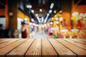 Holztisch auf abstraktem Bokeh des Einkaufszentrums. zur Präsentation oder Montage Ihrer Produkte. foto