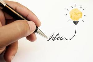 Kreativität Inspiration, Ideen und Innovationskonzepte mit Glühbirne und zerknittertem Papierball. Hand des Geschäftsmannes, der Textidee mit Stift schreibt. foto
