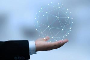 Hand des Geschäftsmannes, der globale Netzwerkverbindung und Erdkugel mit Punkten und Linien hält. foto