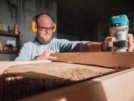 bärtiger Zimmermann, der mit einem elektrischen Fraser arbeitet foto