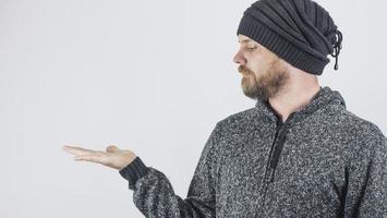 bärtiger Kerl hält seine Handfläche auf einem leeren weißen Hintergrund foto