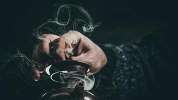männliche Hand schloss den Deckel einer Ton-Teekanne foto