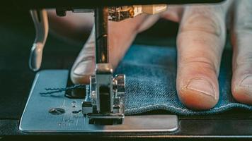 männliche Hand nähen Denim auf einer Nähmaschine foto