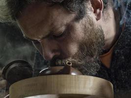 Mann mit Bart atmet Rauch in eine traditionelle Teekanne foto