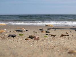 Meereskiesel und Muscheln an der Küste gegen den blauen Himmel foto