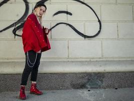 junge Blondine in gestrickter schwarzer Mütze, roter Jacke und roten Schuhen steht unter einer Brücke inmitten von Graffiti foto