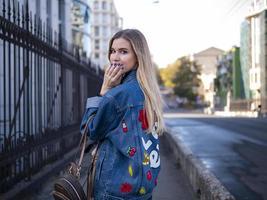 süßes blondes Teen mit wallendem Haar in einer Jeansjacke auf der Brücke im Freien foto