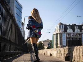 Schönes, stilvolles Teenager-Mädchen mit fließendem Haar in vollem Wachstum auf einer Stadtbrücke foto
