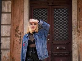 Blondes Model-Mädchen mit fließendem Haar in einer Jeansjacke steht vor dem Hintergrund eines alten Gebäudes mit einer Vintage-Tür foto