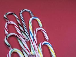 Setzen Sie bunte Karamell-Cane-Blau-Lila-Streifen von Rot-Grün über rosa Hintergrund foto