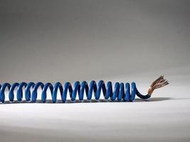blaues Kabel auf weißem Hintergrund verdreht. elektrisch isolierter Draht foto