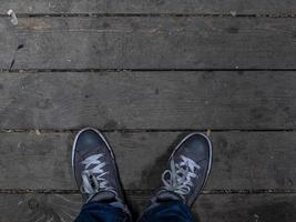 Männerfüße in Turnschuhen stehen auf dem Holzboden. modische Herren Sneakers foto