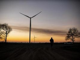Silhouette eines Mannes geht zum Sonnenuntergang in Richtung Windkraftanlagen foto