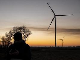 Silhouette eines Mannes bei Sonnenuntergang, der ein Foto von Windturbinen macht. Windkraftanlagen bei Sonnenuntergang