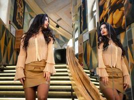 attraktives mädchenmodell mit schönen haaren sieht in einem großen spiegel aus. Fotomodell foto