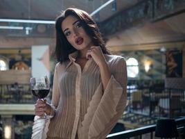 schönes Mädchenmodel posiert stehend mit einem Glas Rotwein in der Hand in einem Restaurant foto