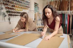 konzentrierte junge Schneider mit Schnittmustern während der Arbeit an der Herstellung von maßgeschneiderten Jacken foto