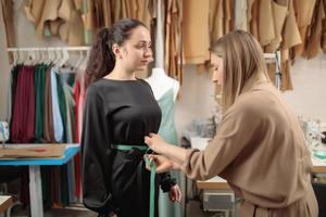 Modemodell, das Kleidung von einem professionellen Designerstudio anpasst und Messungen vornimmt foto