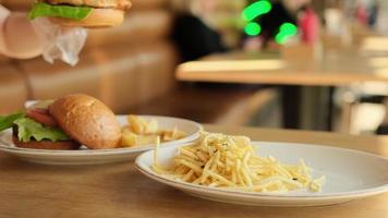 weibliche Hand, die einen Burger von einem Teller in einem Café nimmt. foto