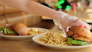 Frau in Handschuhen, die Hamburger zum Essen nimmt foto