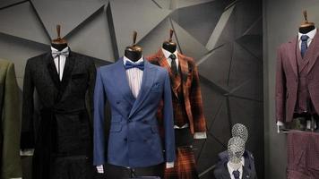 Luxusanzüge für Herren, die auf Schaufensterpuppen im Geschäft angezeigt werden foto
