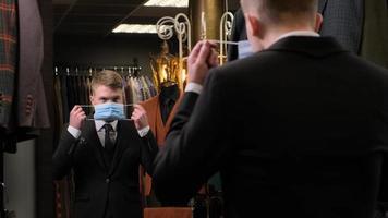 junger Mann, der in einem Herrenbekleidungsgeschäft vor dem Hintergrund von Jacken eine Schutzmaske vor einem Spiegel aufsetzt foto