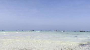 Fischerboote im türkisfarbenen Wasser an einem weißen Sandstrand, der von Wellen geschoben wird. Sansibar, Tansania, Indischer Ozean foto