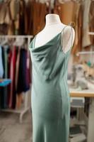 Attrappe, die ein Kleid im Modedesignerstudio trägt, mit professioneller Ausrüstung, Skizzen, Schaufensterpuppe, Stoff foto