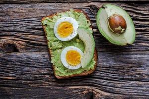 Toast mit Avocadopüree und Eiern auf rustikalem Holztisch mit foto
