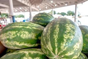Haufen frischer reifer Wassermelonen, die in Holzkisten in Obst liegen lying foto