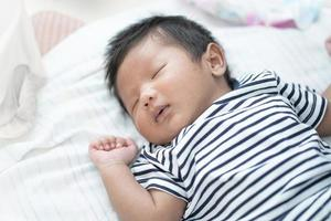 entzückender asiatischer Schlaf, gesunder Schlaf des kleinen Säuglings mit warmer weißer Wolldecke zu Hause, Babygesundheitskonzept foto