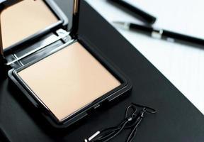 kosmetisches Gesichtspuder im schwarzen quadratischen Behälter und Notizbuchstiftohrringe auf Holztisch foto