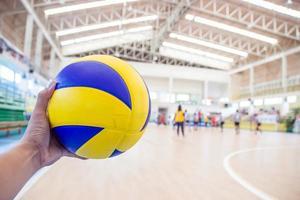 linke Hand hält einen Volleyball für das Volleyballspiel foto