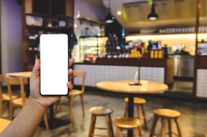 Hand, die Telefonmodell-Bild leerer Bildschirm für Werbetext im Vintage-Café-Café-Hintergrund hält foto