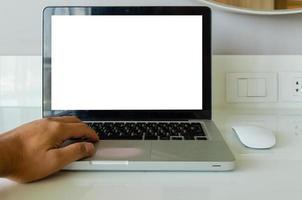 Hand auf Tastatur-Computer-Laptop-Mock-up und Maus weißer leerer Bildschirm für Werbetext auf dem Tisch foto