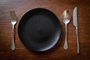 leerer Teller oder Teller mit Messer, Gabel und Löffel auf Holzfliesenhintergrund foto