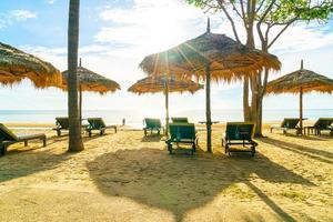 Sonnenschirme und Strandkörbe mit Kokospalmen und Meeresstrandhintergrund und blauem Himmel - Urlaubs- und Urlaubskonzept foto