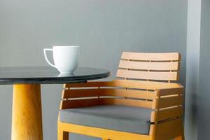 Kaffeetasse auf Tisch mit leerem Stuhl foto