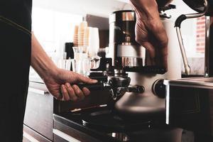 junger asiatischer mann, der kaffeemühlenmaschine verwendet, um kaffeebohnen im café zu grillen. Barista-Konzept foto
