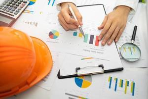 Architekt oder Ingenieur, der Projektabrechnung mit Diagramm mit Werkzeugen im Büro, Baukontokonzept arbeitet. foto