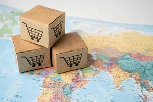 Warenkorb-Logo auf Box auf Weltkugel-Kartenhintergrund. Bankkonto, investitionsanalytische Forschungsdatenökonomie, Handel, Online-Unternehmenskonzept für Geschäftsimport und -export. foto