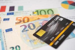 Kreditkarte mit Euro-Banknoten auf Diagramm- und Millimeterpapier. Finanzentwicklung, Bankkonto, Statistik, investitionsanalytische Forschungsdatenwirtschaft, Börsenhandel, Geschäftskonzept. foto