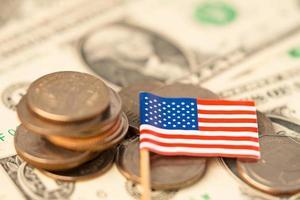 Stapel Münzen mit USA-Amerika-Flagge auf weißem Hintergrund. Flagge auf Dollar-Banknoten. foto