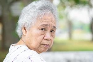 asiatische senior oder ältere alte dame frau, die im park sitzt, gesundes starkes medizinisches konzept. foto