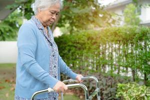 Asiatische Senioren oder ältere alte Damenfrauen verwenden einen Walker mit starker Gesundheit, während sie im Park in einem schönen Urlaub spazieren gehen foto